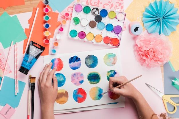 Podwyższony Widok Maluje Kolorowego Abstrakcjonistycznego Okrąg Na Białym Papierze Kobiety Ręka Darmowe Zdjęcia