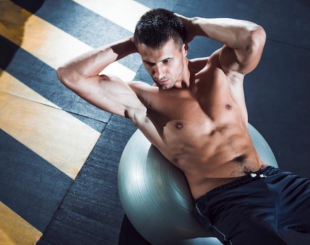 Podwyższony widok młody człowiek ćwiczy na sprawności fizycznej piłce Darmowe Zdjęcia