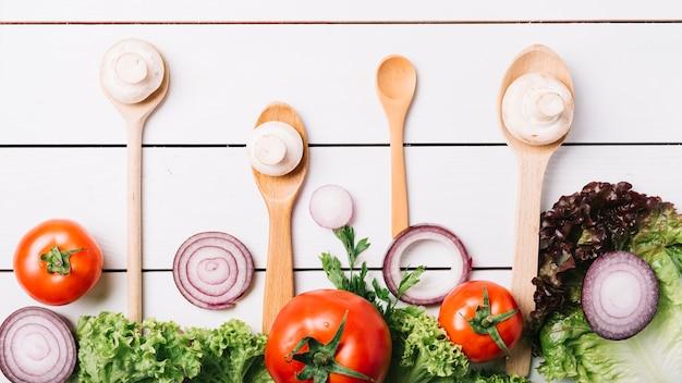 Podwyższony widok świezi warzywa z łyżkami na drewnianym tle Darmowe Zdjęcia