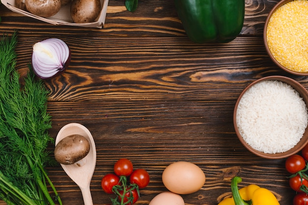 Podwyższony widok warzywa z pucharem ryż groszkuje i polenta na drewnianym stole Darmowe Zdjęcia