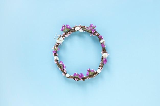 Podwyższony widok wianek robić kwiaty na błękitnym tle Darmowe Zdjęcia