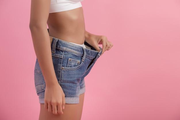 Pojęcie diety i odchudzanie. kobieta w dużych dżinsach Darmowe Zdjęcia