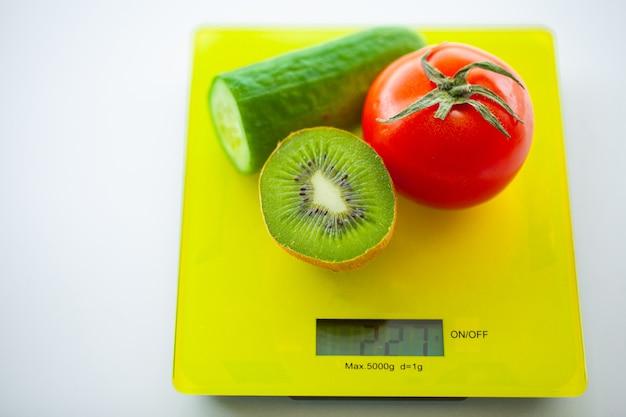 Pojęcie diety lub kontroli wagi. owoce i warzywa z miarą na skali wagi. koncepcja diety fitness i zdrowej żywności. Premium Zdjęcia