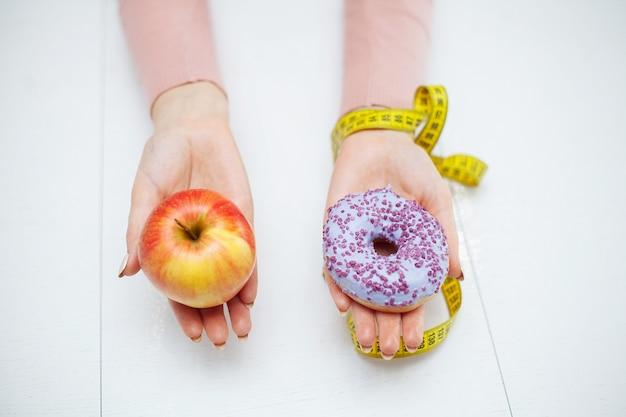 Pojęcie diety, piękna młoda kobieta wybiera między zdrowym jedzeniem i fast foodem Premium Zdjęcia