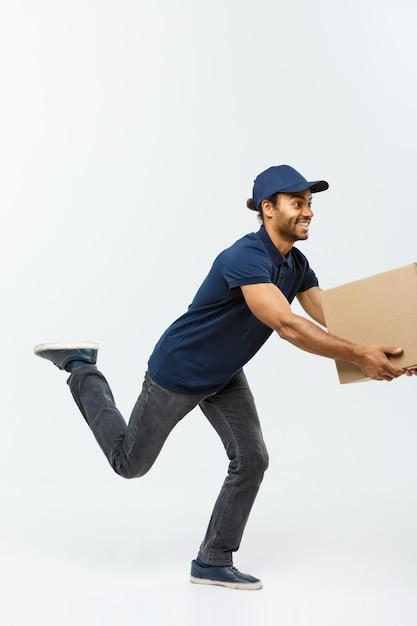 Pojęcie dostawy - przystojny mężczyzna afroamerykanów dostawy rush uruchomiony dla dostarczania pakietu dla klienta. pojedynczo na tle szarym studio. skopiuj miejsce. Darmowe Zdjęcia