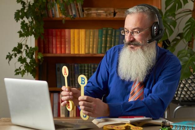 Pojęcie Kształcenia Na Odległość Dla Małych Dzieci. Nauczyciel Uczy Dziecka Czytania I Liczenia Online Za Pomocą Laptopa. Premium Zdjęcia