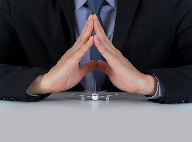 Pojęcie podróży ubezpieczeniowej, ręce wsparcia modelu samolotu na biurku Premium Zdjęcia