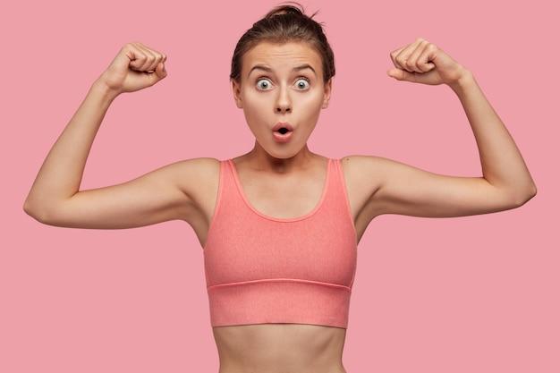 Pojęcie Siły I Feminizmu. Zaskoczona Młoda Europejska Sportsmenka W Różowym Casualowym Topie Pokazuje Mięśnie Dłoni Darmowe Zdjęcia