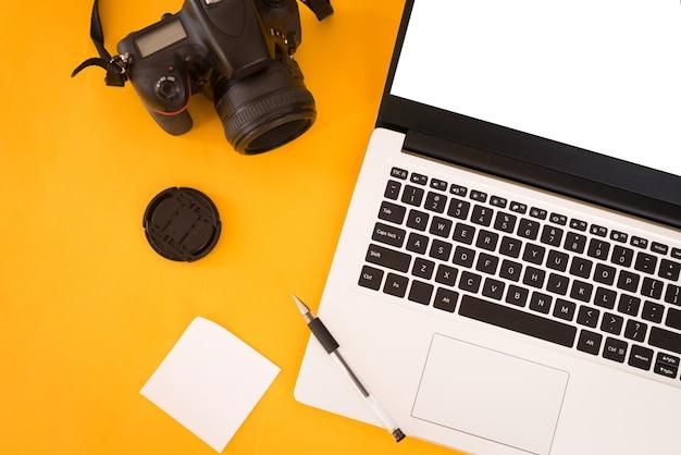 Pojęcie Terminu Fotografa. Widok Z Góry Stołu Projektanta Z Laptopem Pc, Aparatem Fotograficznym, Białymi Naklejkami I Długopisem. Skopiuj Miejsce, żółte Tło. Premium Zdjęcia