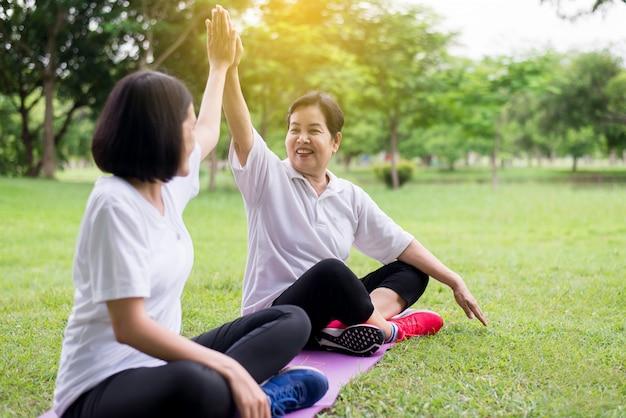 Pojęcie Zdrowego Stylu życia, Azjatyckie Kobiety Razem Podnoszą Ręce I Relaksują Się W Parku, Szczęśliwy I Uśmiechnięty, Pozytywne Myślenie Premium Zdjęcia