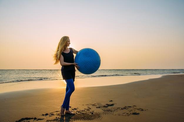 Pojęcie Zdrowego Stylu życia Dla Kobiet. Uśmiechnięta Młoda Kobieta Z Długim Blondynka Włosy Z Dużą Błękitną Piłką Na Tle Opustoszała Plaża Podczas Zmierzchu. Premium Zdjęcia