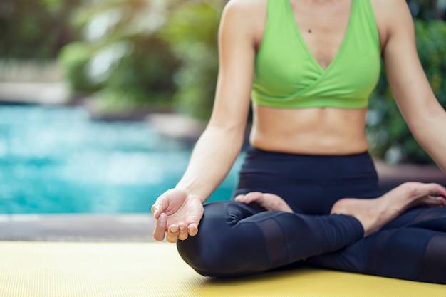 Pojęcie zdrowego stylu życia. kobiety ćwiczy joga poza medytuje w lotosowej pozyci Premium Zdjęcia