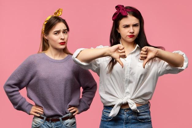 Pojedyncze Ujęcie Dwóch Atrakcyjnych Młodych Kobiet Wyrażających Dezaprobatę, Niechęć, Rozczarowanie Złą Jakością, Pokazując Kciuk W Dół Gest, Niezadowolony Wygląd. Darmowe Zdjęcia