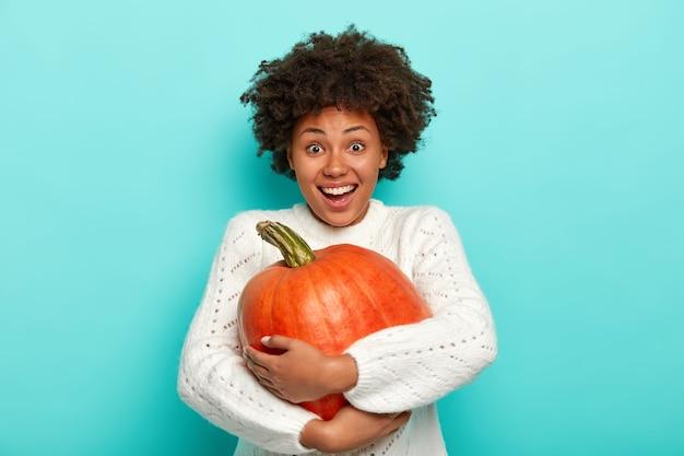 Pojedyncze Ujęcie Szczęśliwej Kobiety Afro Cieszy Się Sezonem Jesiennym, Trzyma Dużą Dojrzałą Dynię, Zbiera Warzywa Z Jesiennego Ogrodu, Ma Radosny Wyraz Twarzy, Nosi Biały Sweter, Modele Na Niebieskim Tle Darmowe Zdjęcia