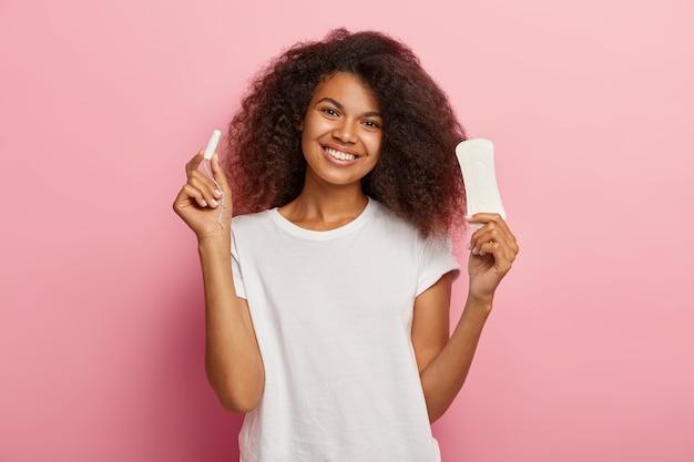 Pojedyncze Ujęcie Szczęśliwej Młodej Kobiety Afro Posiada Tampon Bawełniany Menstuation I Podpaski Higieniczne Darmowe Zdjęcia