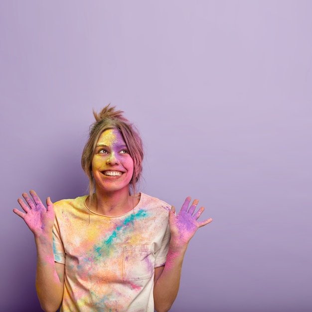 Pojedyncze Ujęcie Zadowolonej, Marzycielskiej Młodej Kobiety, Skierowanej W Górę, Unoszącej Obie Ręce I Pokazującej Kolorowe Dłonie, Uśmiechającej Się Pozytywnie, świętującej święto Kolorów Holi, Wolne Miejsce Powyżej Na Twoje Informacje Darmowe Zdjęcia