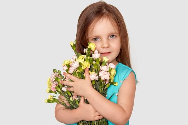 Pojedyncze Zdjęcie Dość Małej Dziewczynki Przygotowuje Bukiet Kwiatów Dla Mamy Na Dzień Matki, Ma Atrakcyjny Wygląd, Ubrane W świąteczne Ubrania, Odizolowane Na Białej ścianie. Koncepcja Wiosny I Dzieci Darmowe Zdjęcia