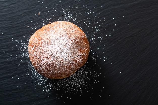 Pojedynczy Koncepcja żywności Beignet Francuskie Drożdżowe Pączki Drożdżowe Smażone W Głębokim Tłuszczu Na Czarnej Płycie łupkowej Premium Zdjęcia