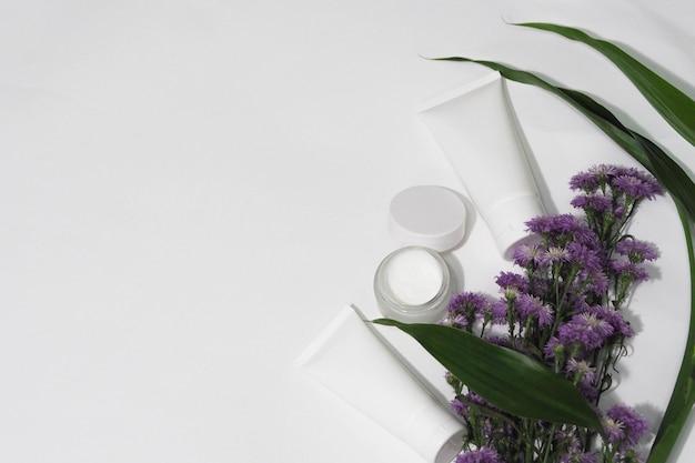 Pojemniki na butelki kosmetyczne biały produkt z kwiatkiem i liściem. Premium Zdjęcia