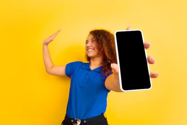 Pokazuje Ekran Telefonu. Portret Kaukaski Nastolatka Na żółtej ścianie. Piękne Kobiece Kręcone Modelki W Koszuli. Pojęcie Ludzkich Emocji, Wyraz Twarzy, Sprzedaż, Reklama, Edukacja. Copyspace. Darmowe Zdjęcia