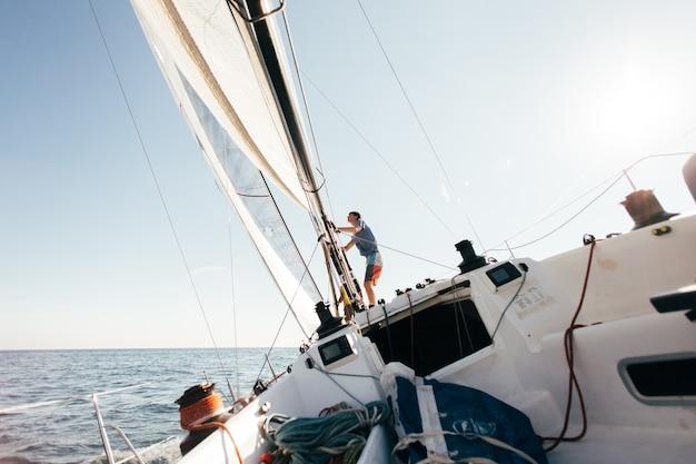 Pokład Profesjonalnej żaglówki Lub Jachtu Regatowego Podczas Zawodów W Słoneczny I Wietrzny Letni Dzień, Szybko Poruszający Się Przez Fale I Wodę, Ze Spinakerem W Górę Darmowe Zdjęcia
