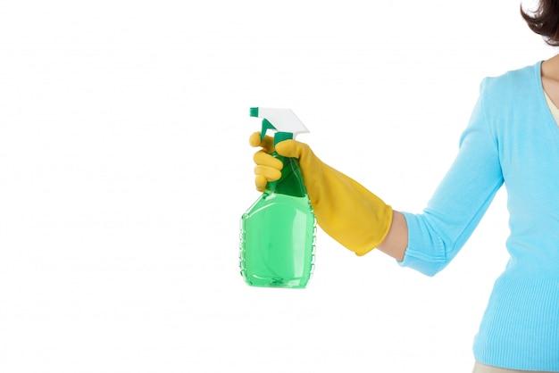 Pokojówka stojąca z wyciągniętą ręką trzymającą butelkę z detergentem w sprayu Darmowe Zdjęcia