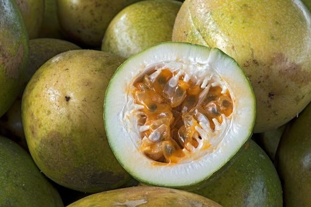 Pokrojony kwaśny owoc marakui, nad stosem całych owoców Premium Zdjęcia