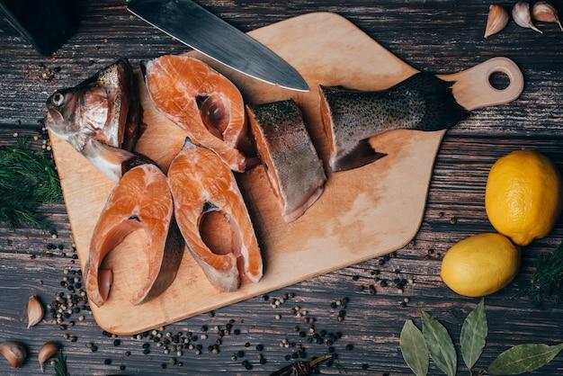 Pokrojony pstrąg na drewnianym stole z cytryną i przyprawami Premium Zdjęcia
