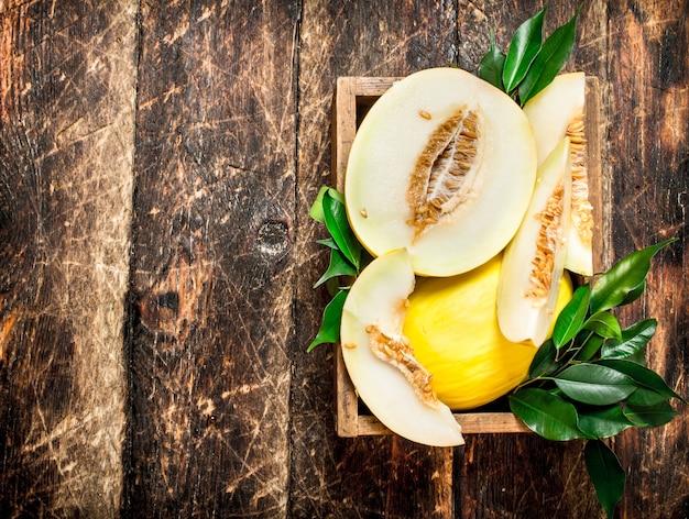Pokrojony świeży Melon W Starym Pudełku. Na Drewnianym Tle. Premium Zdjęcia