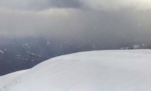 Pokryte śniegiem górskie wzgórza karpackie z turystami daleko turystów w zimie Premium Zdjęcia