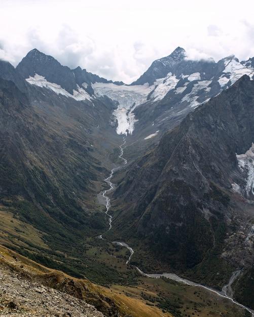 Pokryte śniegiem Pasmo Górskie W Chmurach. Dolina Z Górskim Potokiem. Kaukaz, Rosja Premium Zdjęcia