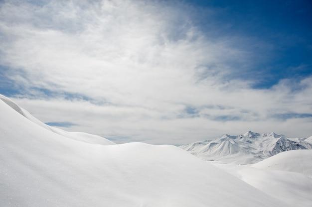 Pokrywa śnieżna I Ośnieżone Szczyty Górskie Na Tle Błękitnego Nieba Premium Zdjęcia
