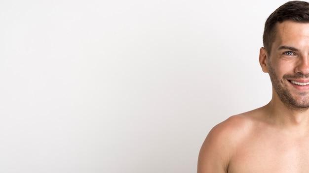 Pół twarzy bez koszuli uśmiechnięta młody człowiek pozycja przeciw białemu tłu Darmowe Zdjęcia