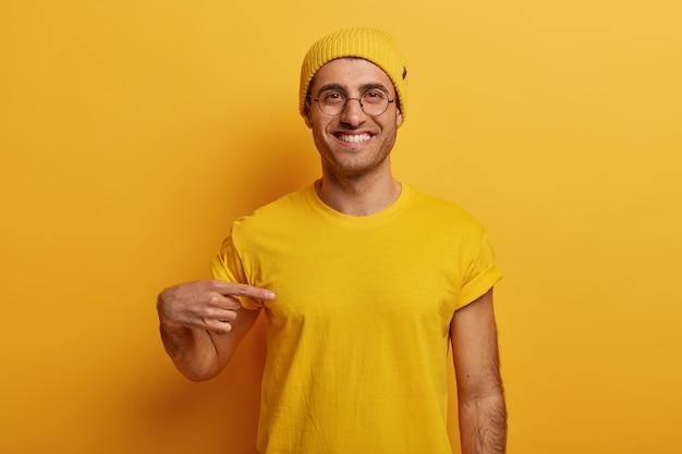 Półdługie Ujęcie Wesołego Mężczyzny Wskazuje Na żółtą Koszulkę, Ma Zadowoloną Minę, Reklamuje Nowy Strój, Pozuje Na Jasnym Tle Darmowe Zdjęcia