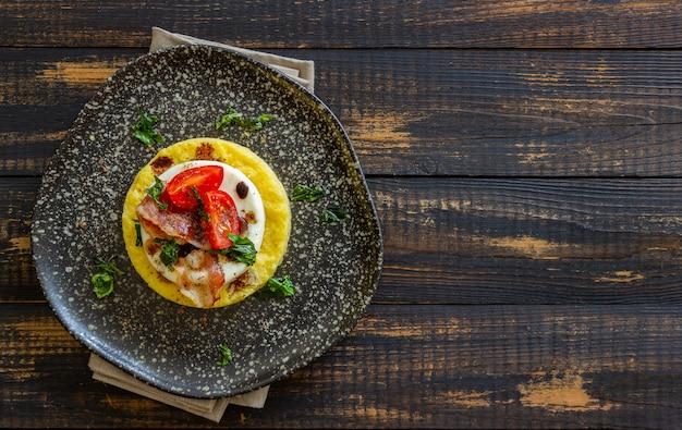 Polenta Z Mozzarellą, Boczkiem I Pomidorami Premium Zdjęcia