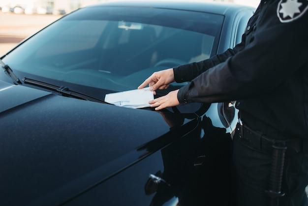 Policjant w mundurze wypisuje mandat na drodze Premium Zdjęcia