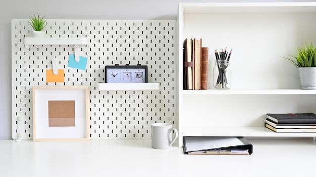 Półki i tablica z artykułami biurowymi na stole roboczym Premium Zdjęcia