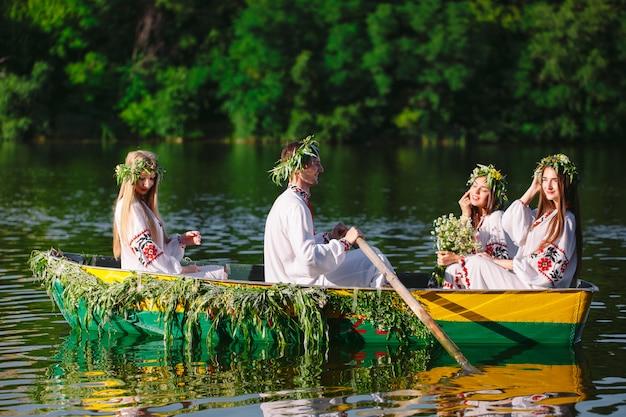 Połowa lata. grupa młodych ludzi w strojach ludowych pływa łodzią ozdobioną liśćmi i porostami. słowiańskie święto iwana kupały. Premium Zdjęcia