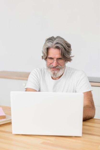 Połowa Strzał Nauczyciela Przy Biurku Za Pomocą Laptopa Darmowe Zdjęcia