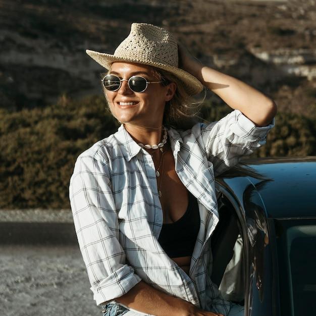 Połowa Strzału Blondynka Kobieta Stojąca Przez Okno Samochodu Darmowe Zdjęcia