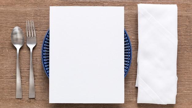Połóż Płasko Pusty Papier Menu Na Talerzu Ze Sztućcami I Serwetką Premium Zdjęcia