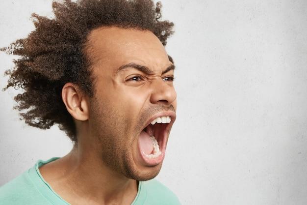 Półprofil Agresywnego Mężczyzny Z Ciemnymi Kręconymi Włosami, Szeroko Otwartymi Ustami, Wrzeszczącym W Panice Darmowe Zdjęcia