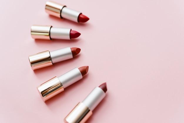 Pomadki w różnych odcieniach różu i czerwieni leżą na pastelowym różowym tle. copyspace, widok z góry Premium Zdjęcia