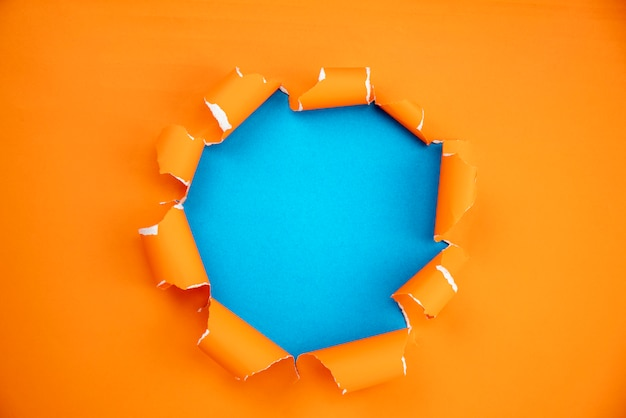 Pomarańcze rozdzierał otwartego papier na błękitnego papieru tle Premium Zdjęcia