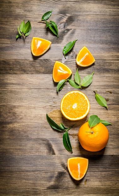 Pomarańcze świeże W Całości, Cięte I Liście. Na Drewnianym Stole. Widok Z Góry Premium Zdjęcia