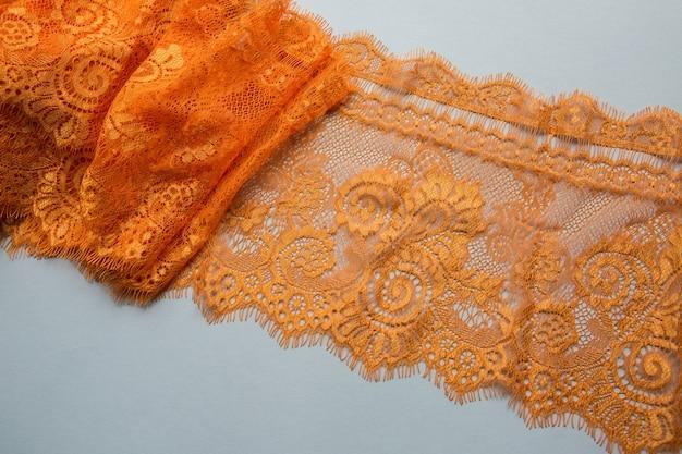 Pomarańczowa Koronka Leżąca Na Białej Powierzchni Premium Zdjęcia