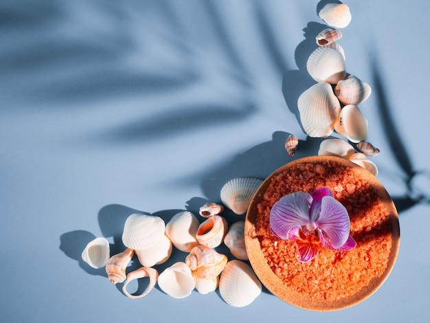 Pomarańczowa Sól Do Kąpieli W Spodku Ze Skorupkami I Kwiatkiem Na Niebieskim Tle Z Cieniem Tropikalnej Rośliny. Copyspace, Płaski. Spa, Relaks, Lato Premium Zdjęcia