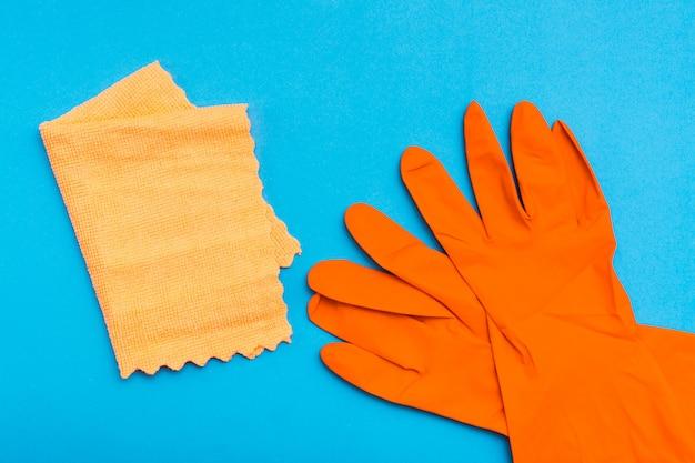 Pomarańczowe gumowe rękawiczki i żółta szmata z mikrofibry na niebieskim tle Premium Zdjęcia