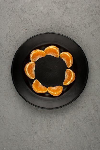 Pomarańczowe Mandarynki Pokrojone Na łagodne Soczyste Dojrzałe Widok Z Góry W Czarnym Talerzu Na Szarym Biurku Darmowe Zdjęcia