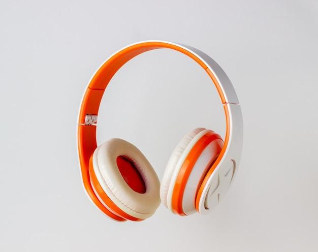 Pomarańczowe Słuchawki Na Białej ścianie Premium Zdjęcia